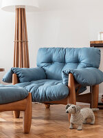 Comfortably armchair with squashy blue cushions, standard lamp and toy dachshund