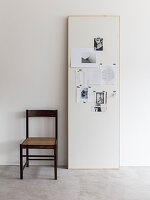 Chair next to wooden panel used as pin board