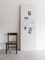 Stuhl neben Holzpaneel als Pinnwand