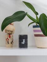 Zimmerpflanze und asiatische Holzpuppe auf Ablage