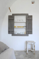 Shelving in niche with shutters in living room