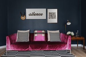 Pink, velvet couch with scatter cushions on black-and-white striped rug against dark wall