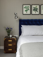 Double bed with deep-blue headboard, wall-mounted lamp and bedside cabinet in bedroom