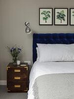 Doppelbett mit Bettkopfteil, Wandleuchte und Nachtkästchen im Schlafzimmer
