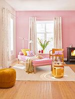 Daybed, Stuhl, Holzofen, goldfarbener Beistelltisch und Pouf im Wohnzimmer in Rosatönen