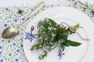 Kräutersträusschen aus Bergminze und Borretsch auf Teller liegend