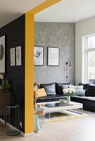 Blick auf schwarze Ledercouch an grauer Wand in offenem Wohnraum