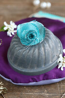 Turquoise fabric flowers on small bundt-cake tin