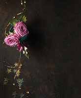 Festive arrangement of pink roses, fairy lights and gold stars