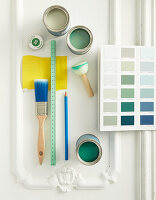 Painting utensils and white and green paints