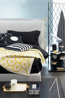 Schwarz-weiße Bettwäsche und gelbe Decke auf weißem Doppelbett mit Bettkopfteil