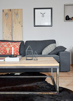 Grey couch against wooden panel on wall behind candles and metal house-shaped ornaments on coffee table in living room