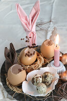 Easter arrangement of small straw nests, Easter bunnies made from folded napkins, quail eggs in ceramic dish and lit candle
