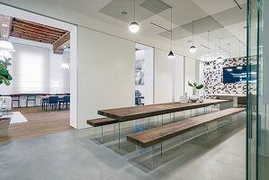 Langer Holzesstisch mit dazupassenden Sitzbänken in offenem Wohnraum mit geschliffenem Betonboden