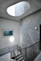 Stairwell with metal banisters, skylight and concrete wall