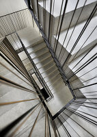 Concrete staircase with metal banisters in stairwell (view from top)