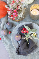 Autumnal arrangement with rose hips and figs on table