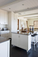 Island counter in open-plan kitchen with white panelled cabinets