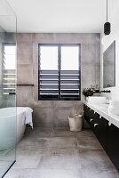 Doppelwaschtisch, frei stehende Badewanne und Fliesen im Industrie-Look im Badezimmer