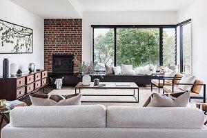 Verschiedene Sitzmöbel, Kamin mit Backsteinwand und Fensterfront im Wohnzimmer