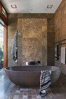 Frei stehende Badewanne im Badezimmer mit Travertin-Fliesen