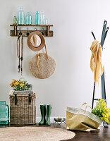 Wandgarderobe mit Flaschensammlung, Hut und Handtasche, darunter Korbtruhe und Gummistiefel, daneben Garderobenständer
