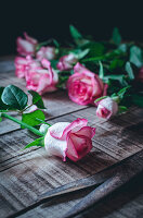 Soft pink roses on rough wooden table