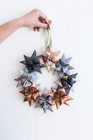 Hand holding Christmas wreath of origami stars