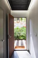 Blick durch geöffnete Haustür in Vorgarten