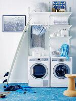 Waschmaschine und Trockner, darüber weiße Regale im Waschraum mit hellblauen Zementfliesen