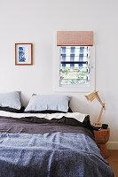 Doppelbett und Nachttisch mit Gelenklampe unter kleinem Fenster
