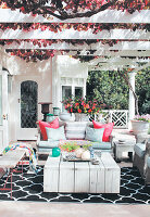 Wooden furniture and rug in seating area blow pergola
