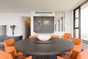 Chairs with orange upholstery at round dining table