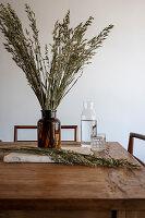Getreideähren in Apothekerflasche und Glaskaraffe auf rustikalem Holztisch