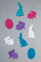 Strings of paper Easter eggs and Easter bunnies