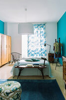 Vintage furniture in bedroom with bright blue walls