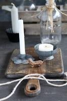 Kerzen in Haltern aus Metall auf einem Schneidebrettchen