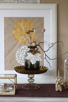 Dried flowers in vase, poppy seed heads and origami leaves
