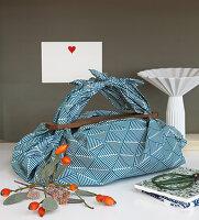 In blau gemusterten Stoff verpacktes Geschenk