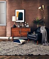 Tischlampe und Getränke auf Retro Sideboard, Ledersessel und Sehleuchte im Zimmer mit dunkler Holzverkleidung