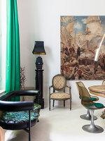 Schwarze Lederbank, Tischlampe auf Säule, Stuhl und Gemälde im Essbereich mit Klassikerstühlen