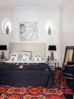 Doppelbett mit Designerkissen und dunkler Tagesdecke im Schlafzimmer, bunter Teppich auf dem Boden