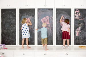 Children drawing on cupboards with chalkboard doors