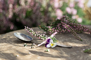 Teaspoon with sprigs of heather and viola flower