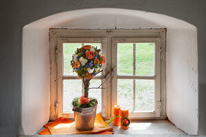 Tree-shaped flower arrangement on sill of rustic window
