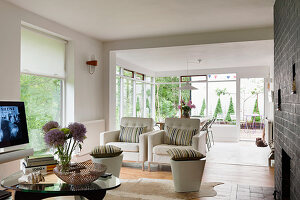 Pair of buttoned white armchairs in open plan living space with exposed brick wall and sun room