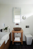 Stone bowl washbasin with wood stand in bathroom with slate floor tiles