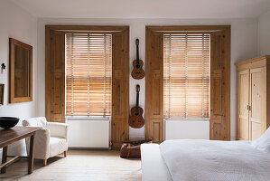 Classical guitars hung up on wall of bedroom with pine window shutters and white armchair