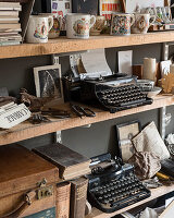 Old typewriters, coronation cups and assorted books on open shelving