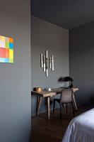Papierkunst über Holztisch mit schwarzer Tischlampe und Stuhl im Schlafzimmer mit grauen Wänden